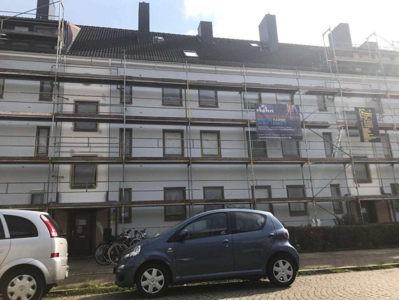 Eingerüstete Fassade mit Firmenschild von Maler Hahn